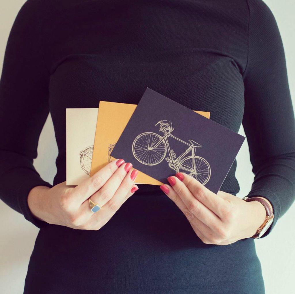 meisje houdt kaarten met fietsen in haar handen